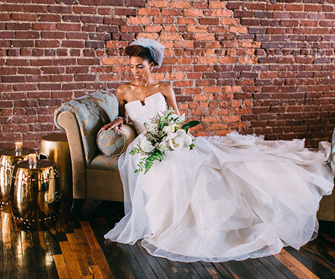 beautiful bride lounging on chaise with Terminus 330's brick background